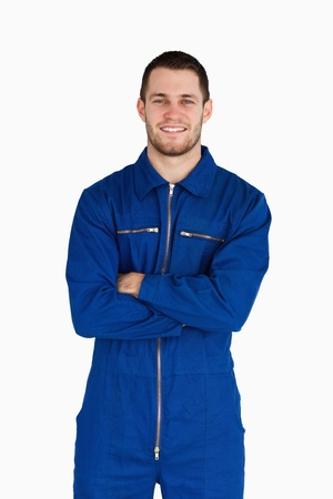 studio happy overall: Smiling mechanic in boiler suit with folded arms against a white background