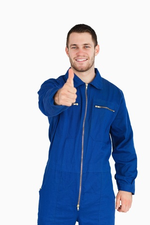 Smiling young mechanic in boiler suit giving thumb up against a white background photo