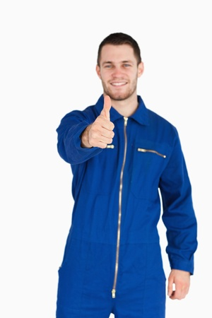 boiler suit: Thumb up given by smiling young mechanic in boiler suit against a white background