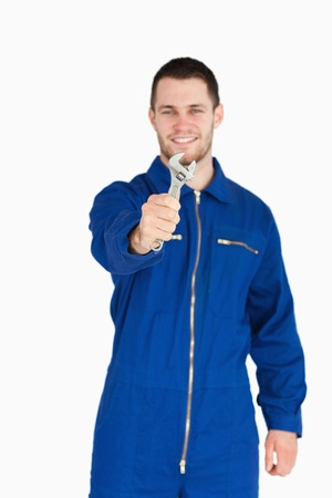 Wrench shown by smiling young mechanic in boiler suit against a white background photo