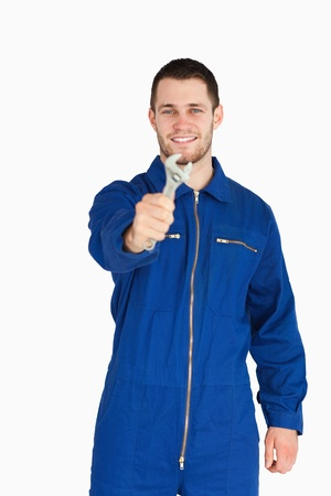 Smiling young mechanic in boiler suit showing a wrench against a white background photo