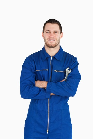 Smiling young mechanic in boiler suit with wrench and arms folded against a white background photo