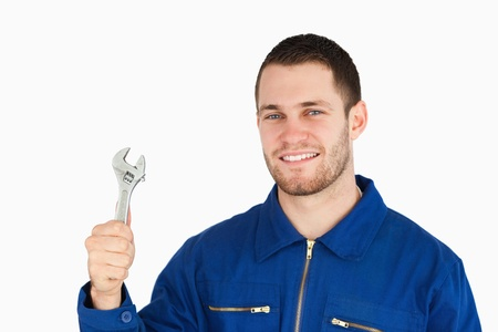Smiling young mechanic holding his wrench against a white background photo