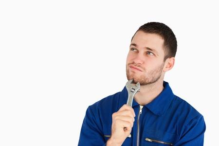 doute: Jeune m�canicien en bleu de chauffe penser contre un fond blanc