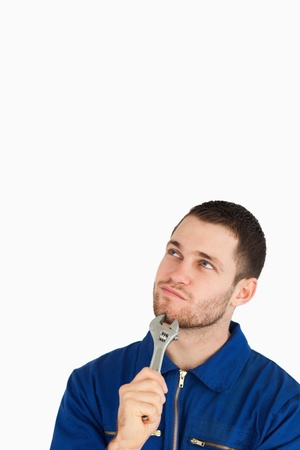 Young mechanic in boiler suit in thoughts against a white background photo
