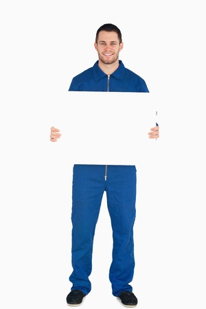 Smiling young mechanic in boiler suit holding a banner against a white background photo