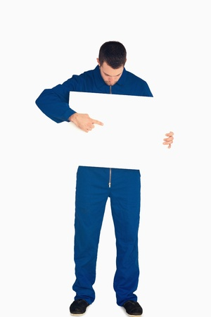 boiler suit: Young mechanic in boiler suit pointing on banner in his hands against a white background Stock Photo