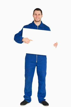 Smiling young mechanic in boiler suit pointing on banner in his hands against a white background photo