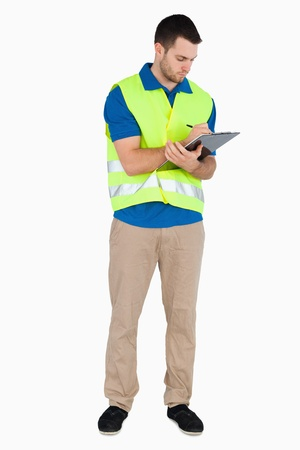 Young male with safety jacket taking notes against a white background photo