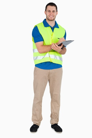 Smiling young male with safety jacket taking notes against a white background photo