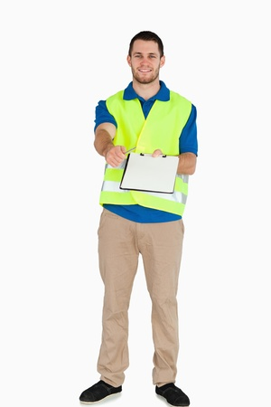 Smiling male in safety jacket handing his notes over against a white background photo