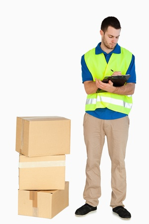 filling in: Young delivery man filling in delivery note against a white background Stock Photo
