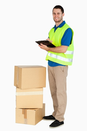 Side view of smiling young delivery man against a white background photo