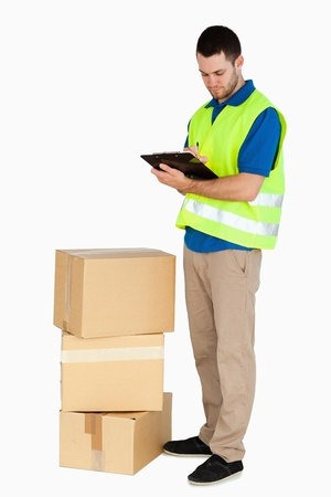 filling in: Side view of young delivery man filling in delivery note against a white background Stock Photo