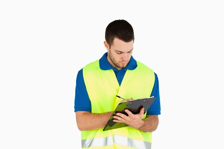 Young delivery man filling in bill of delivery against a white background Stock Photo - 11623734