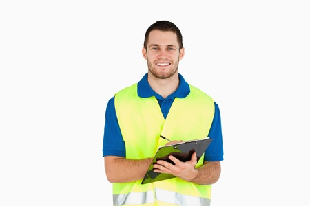 Smiling young delivery man completing delivery note against a white background photo