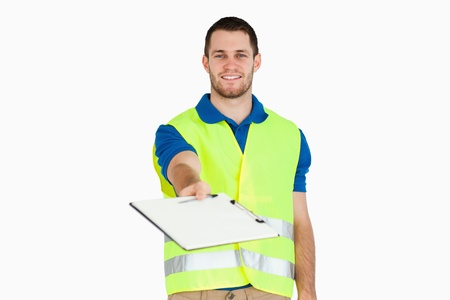 Smiling young delivery man asking for signature on delivery bill against a white background photo