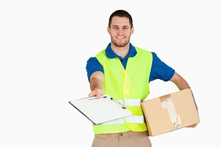 Smiling young delivery man with parcel asking for signature against a white background photo