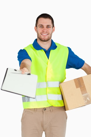 Smiling young delivery man with packet asking for signature against a white background photo