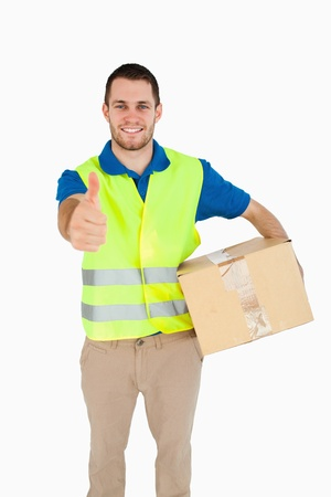 Smiling young delivery man giving thumb up against a white background photo