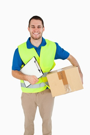 Smiling young delivery man with parcel and delivery note against a white background photo