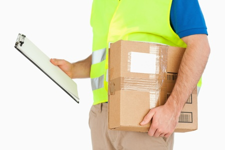 Side view of delivery man with delivery note and parcel against a white background photo