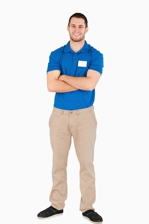Smiling young salesman with arms folded against a white background photo