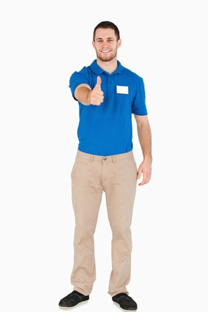 Smiling young salesman giving thumb up against a white background photo