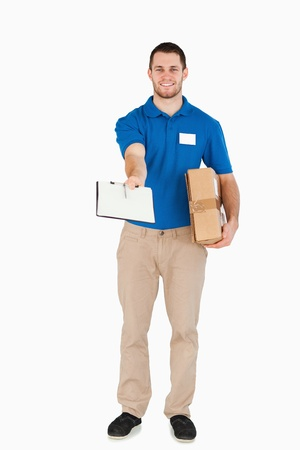 Smiling young salesman with parcel asking for signature against a white background photo