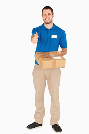 Smiling young salesman with parcel giving thumb up against a white background photo