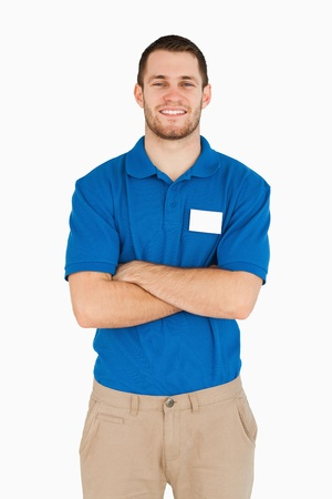 Smiling young salesman with folded arms against a white background photo