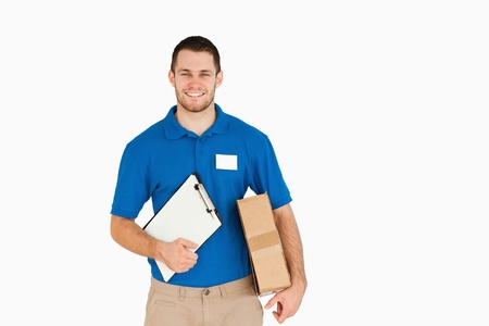 Smiling young salesman with parcel and clipboard against a white background photo