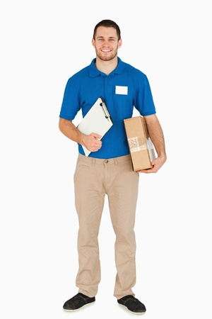 Smiling young salesman with clipboard and parcel against a white background photo