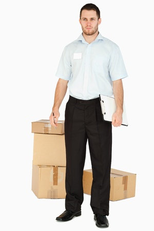 Young post employee with parcels and clipboard against a white background Stock Photo - 11624743