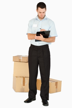 Young post employee with parcels taking notes on his clipboard against a white background photo