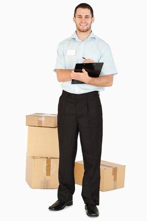 Smiling young post employee with parcels and clipboard against a white background photo