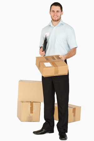 Smiling young post employee with clipboard handing over parcel against a white background photo