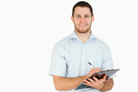 Smiling young post employee taking notes on clipboard against a white background photo