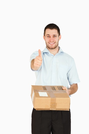 Smiling young post employee handing over parcel while giving thumb up against a white background photo