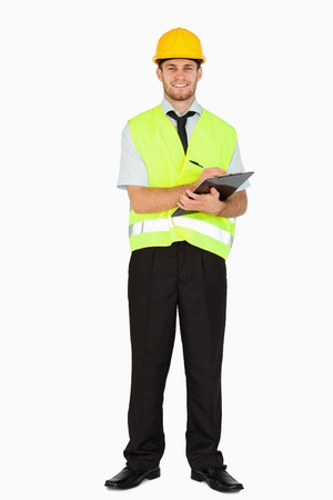 Smiling young foreman in safety jacket taking notes on his clipboard against a white background photo