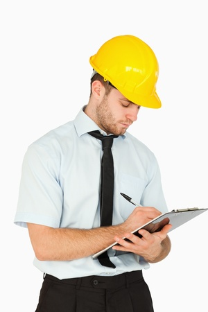 Young lead worker writing on his clipboard against a white background photo