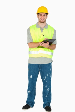 craftman: Smiling young construction worker taking notes against a white background