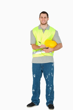 craftman: Smiling young construction worker with clipboard against a white background