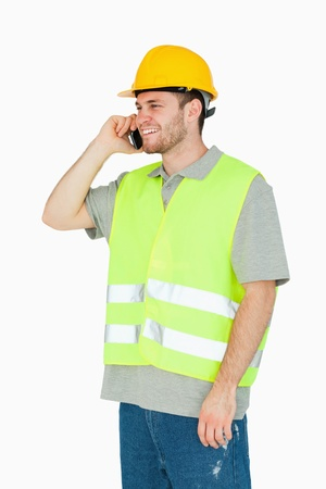 craftman: Smiling young construction worker on the cellphone against a white background