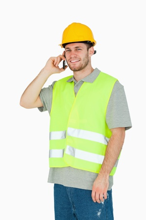 Smiling young construction worker on the mobile phone against a white background photo