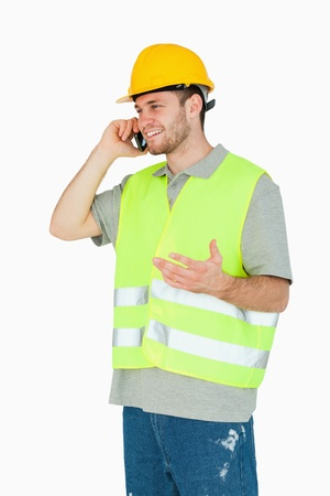 Smiling young construction worker discussing on the cellphone against a white background photo