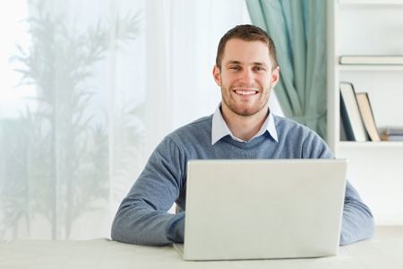 Happy smiling young businessman working in his homeoffice photo
