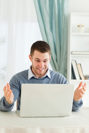 Young businessman surprised about his laptop in his homeoffice photo