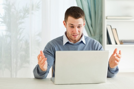 clueless: Young businessman clueless about his laptop in his homeoffice Stock Photo