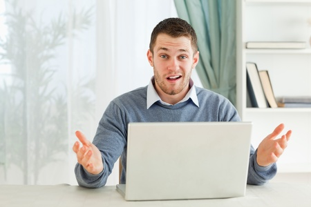 Young businessman clueless about his notebook in his homeoffice photo